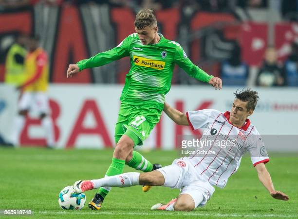 Mickael Cuisance of Moenchengladbach is attacked by Florian Neuhaus of Duesseldorf during the DFB Cup match between Fortuna Duesseldorf and Borussia...