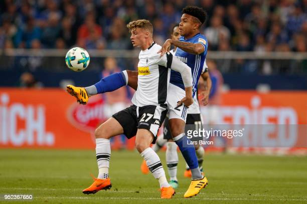 Mickael Cuisance of Moenchengladbach is challanged by Weston McKennie of Schalke during the Bundesliga match between FC Schalke 04 and Borussia...