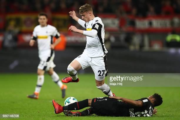 Mickael Cuisance of Moenchengladbach jumps over Wendell of Bayer Leverkusen during the Bundesliga match between Bayer 04 Leverkusen and Borussia...