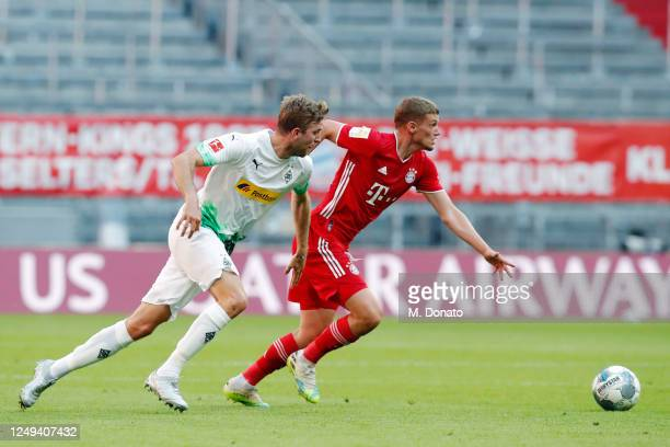 Mickael Cuisance of Muenchen is challenged by Christoph Kramer of Moenchengladbach during the Bundesliga match between FC Bayern Muenchen and...