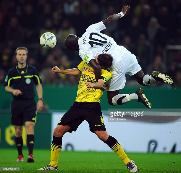 Mickael Pote of Dresden jumps over Sebastian Kehl of Dortmund during the second round DFB Cup match between Borussia Dortmund and Dynamo Dresden at...