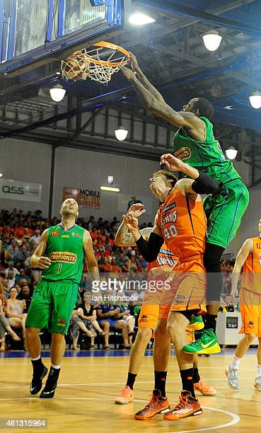 Mickell Gladness of the Crocodiles slam dunks the ball over Alex Loughton of the Taipans during the round 14 NBL match between the Townsville...