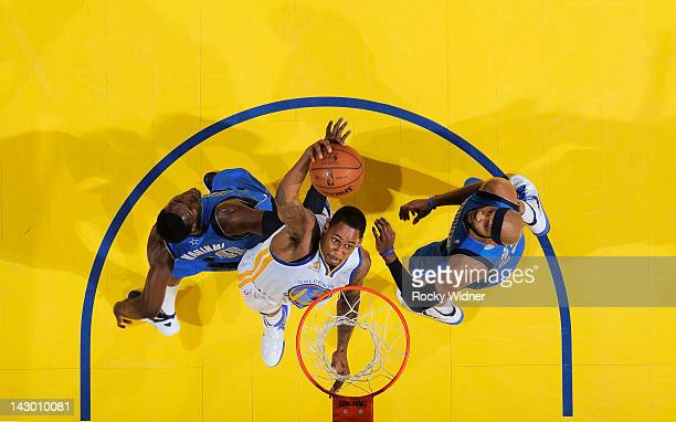 Mickell Gladness of the Golden State Warriors goes up for the dunk against Ian Mahinmi and Vince Carter of the Dallas Mavericks on April 12, 2012 at...