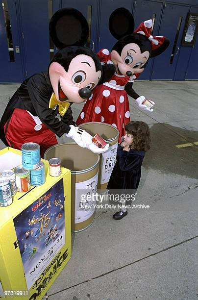 Mickey and Minnie Mouse accept a food donation from Marisa Cumello at the opening night food drive of Disney on Ice at the Continental Airlines Arena...