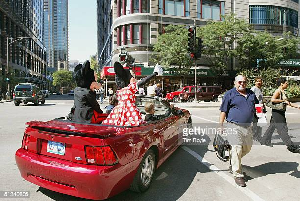 Mickey and Minnie Mouse are seen in traffic as they turn towards the Disney Store September 23 2004 in Chicago Outside the Disney Store a Mickey...