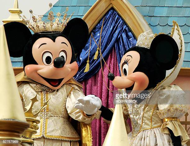 """Mickey and Minnie Mouse hold hands as they parade down Main Street, USA in the """"Walt Disney's Parade of Dreams,"""" the largest gathering of Disney..."""