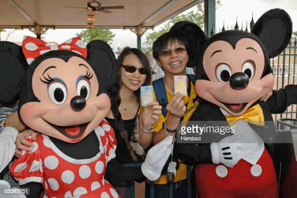 Mickey and Minnie Mouse join Gina So and Jeff Chan as they display their tickets at the turnstiles as Hong Kong Disneyland commence a month of...
