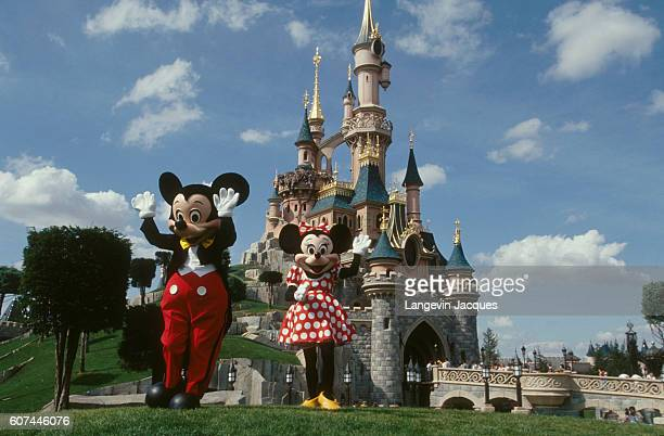 Mickey and Minnie Mouse stand outside Sleeping Beauty Castle at Disneyland Paris