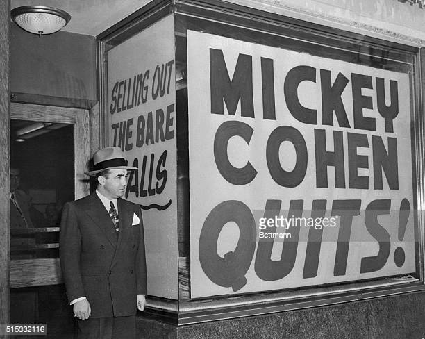 Mickey Cohen stands by the signs in the windows of his exclusive Sunset Strip men's shop Cohen was forced to sell his place to meet the $75000 bail...