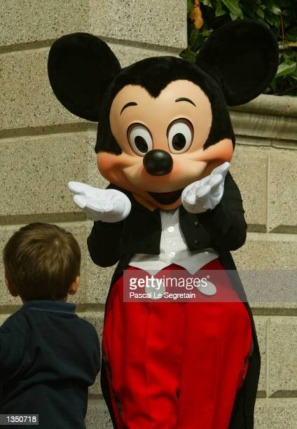 Mickey gives a kiss to a young child in main street at Disneyland Paris August 22 2002 in Marne la Vallee France After a rocky start ten years ago...