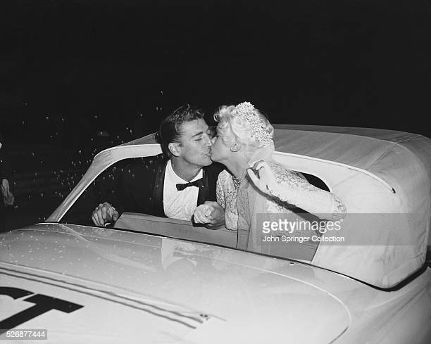 Mickey Hargitay and Jayne Mansfield lean out of their convertible and kiss following their wedding ceremony