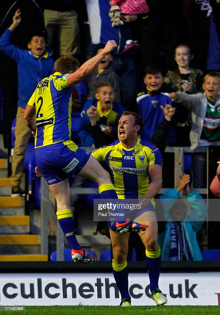 Mickey Higham (R) of Warrington celebrates his try with team mate Chris Riley during the Super League match between Warrington Wolves and Wigan Warriors at the Halliwell Jones Stadium on June 24, 2013 in Warrington, England.