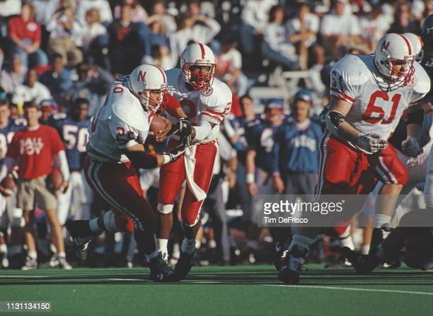 Mickey Joseph, Quarterback for the University of Nebraska Cornhuskers hands the ball off to running back Omar Soto during the NCAA Big 8 Conference...