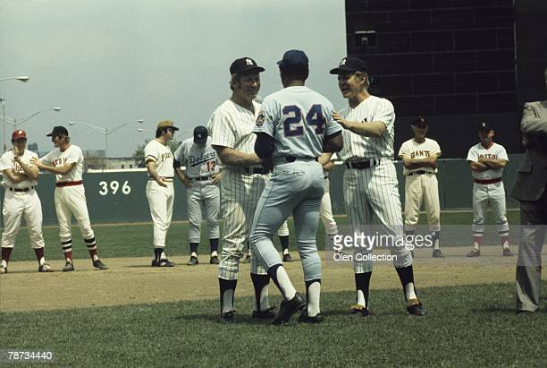 Mickey Mantle and Whitey Ford of the New York Yankees are greeted by Willie Mays of the New York Mets during Old Timers Day ceremonies prior to a...