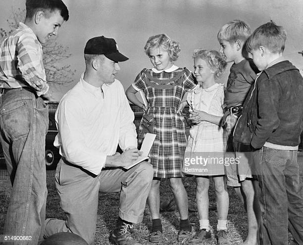 Mickey Mantle is shown here signing autograph books for some of the neighbor's kids on Commerce Oklahoma High School football field