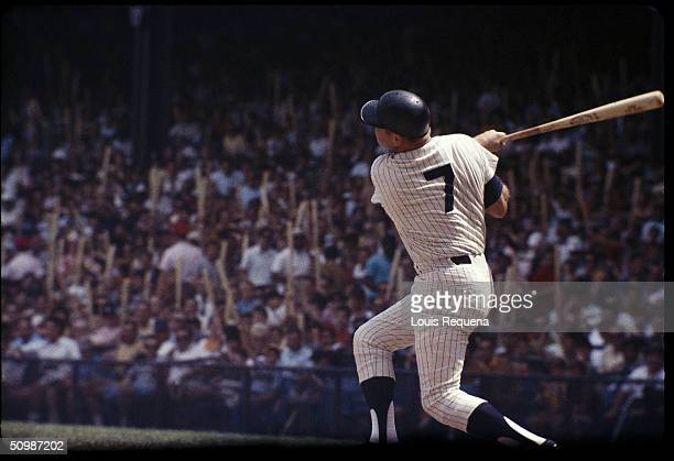 Mickey Mantle of the New York Yankees watches the flight of the ball as he follows through on a swing during a game at Yankee Stadium in Bronx New...
