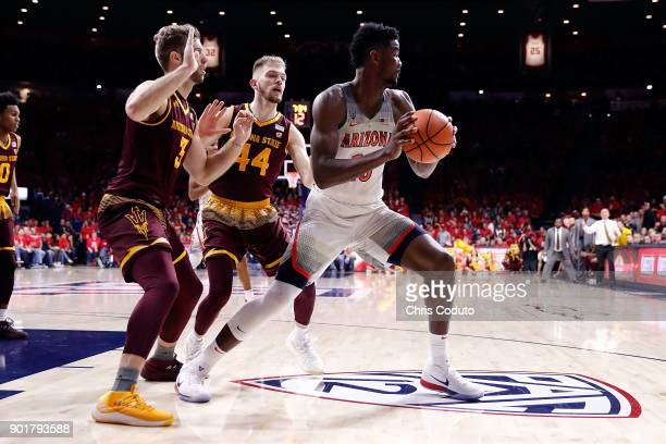 Mickey Mitchell and Kodi Justice of the Arizona State Sun Devils defend Deandre Ayton of the Arizona Wildcats during the second half of the college...
