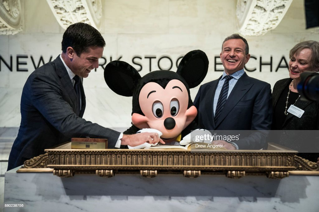 Mickey Mouse and chief executive officer and chairman of The Walt Disney Company Bob Iger sign the guest book before ringing the opening bell at the New York Stock Exchange (NYSE), November 27, 2017 in New York City. Disney is marking the company's 60th anniversary as a listed company on the NYSE.
