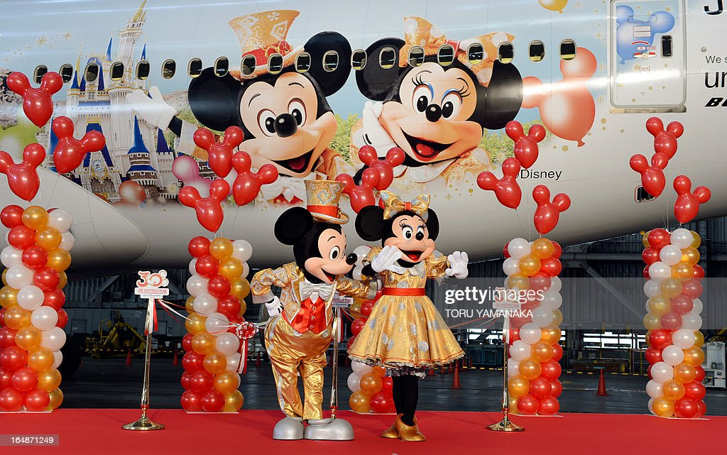 Mickey Mouse (L) and Minnie Mouse mascots introduce a Boeing 777-200 plane decorated with Disney characters (back) at a hangar of Japan Airlines at Haneda Airport in Tokyo on March 29, 2013. JAL unveiled the special plane for domestic flights on March 29, ahead of the 30th anniversary of the Tokyo Disneyland on April 15. AFP PHOTO / Toru YAMANAKA