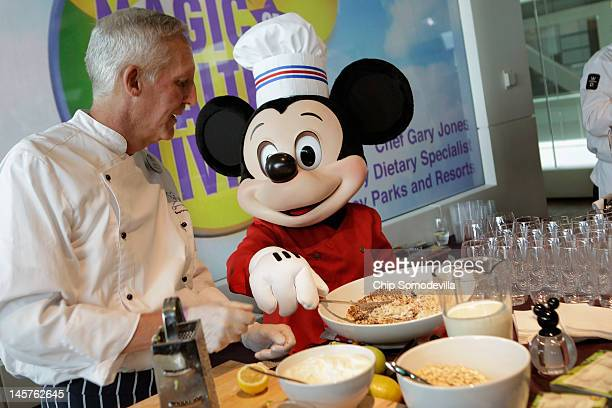 Mickey Mouse character assists Walt Disney Parks and Resorts Culinary Dietary Specialist Gary Jones make healthy smoothies during an event...