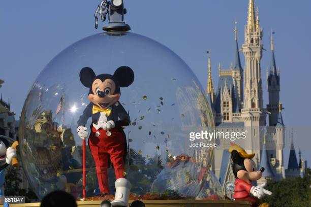 Mickey Mouse rides in a parade through Main Street, USA with Cinderella's castle in the background at Disney World's Magic Kingdom November 11, 2001...