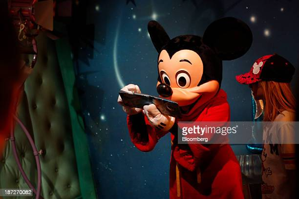 Mickey Mouse signs an autograph at Walt Disney Co's Disneyland Park part of the Disneyland Resort in Anaheim California US on Wednesday Nov 6 2013...