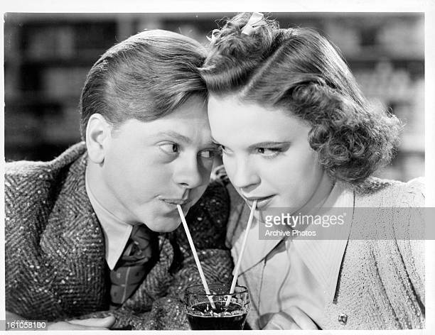 Mickey Rooney and Judy Garland sharing a soda together as they stare into one an others eyes in a scene from the film 'Babes In Arms' which was...