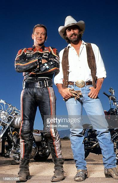 Mickey Rourke and Don Johnson stand in front of their bike in publicity portrait for the film 'Harley Davidson And The Marlboro Man' 1991