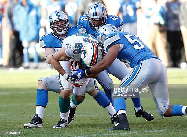 Mickey Shuler of the Miami Dolphins is gang tackled by DeAndre Levy Eric King and Bobby Carpenter of the Detroit Lions on December 26 2010 at Sun...
