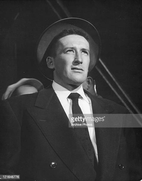 Mickey Spillane standing in a suit and hat in a scene from the film 'Ring Of Fear' 1954