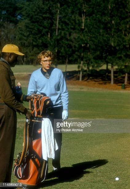 Mickey Wright of the United States chooses a club as her caddie holds her golf bag during the 1956 Titleholders Championship on March 26 1956 at...