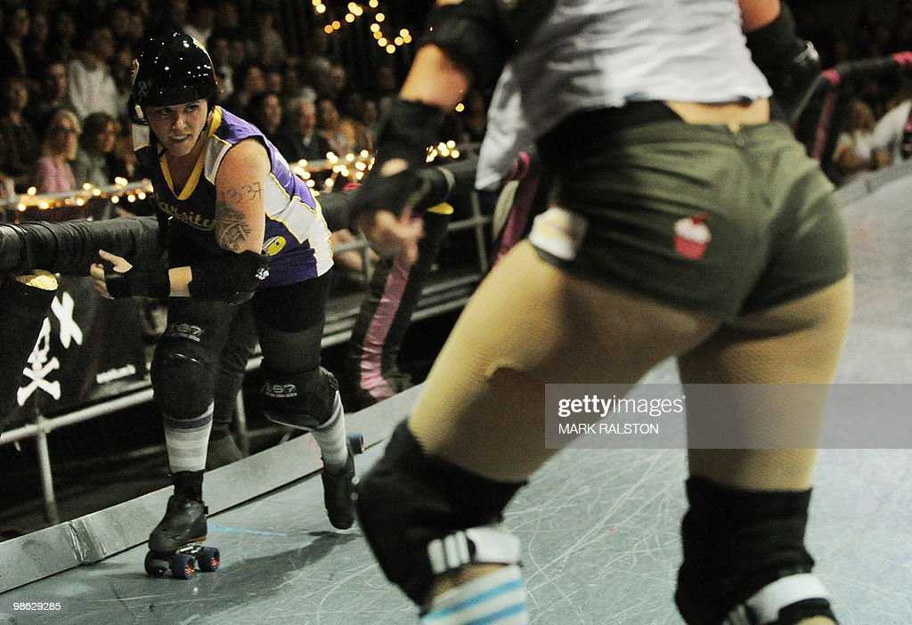 Mickispeedia (L) from the Varsity Brawlers team tries to get past a member of the Tough Cookies team during the L.A. Derby Dolls women's banked track roller derby event in Los Angeles on April 17, 2010. Roller Derby is a contact sport that originated in America and is based on two teams formation roller skating around an oval track, with points scored as one player known as a jammer laps members of the opposing team. The sport which began in 1922 is played predominantly by women skaters with a strong emphasis on punk aesthetics, unique costumes and humorous stage names. AFP PHOTO/Mark RALSTON