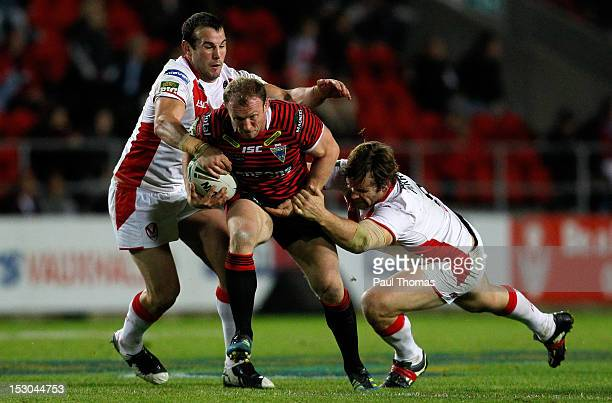 Micky Higham of Warrington is tackled by Anthony Laffranchi and Josh Perry during the Stobart Super League play off match between St Helens and...