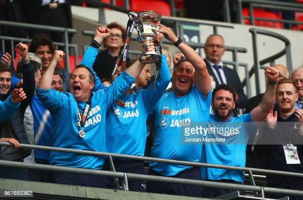 Micky Mellon manager of Tranmere Rovers lifts the trophy with coaching staff as they celebrate victory after during the Vanarama National League Play...