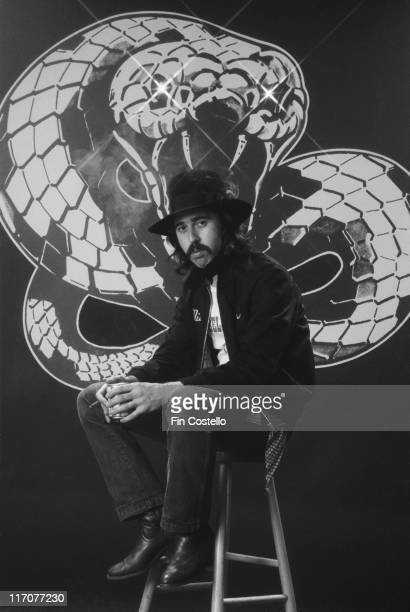 Micky Moody guitarist with British rock band Whitesnake poses sitting on a stool in front of the band's snake logo for a studio portrait in Camden...