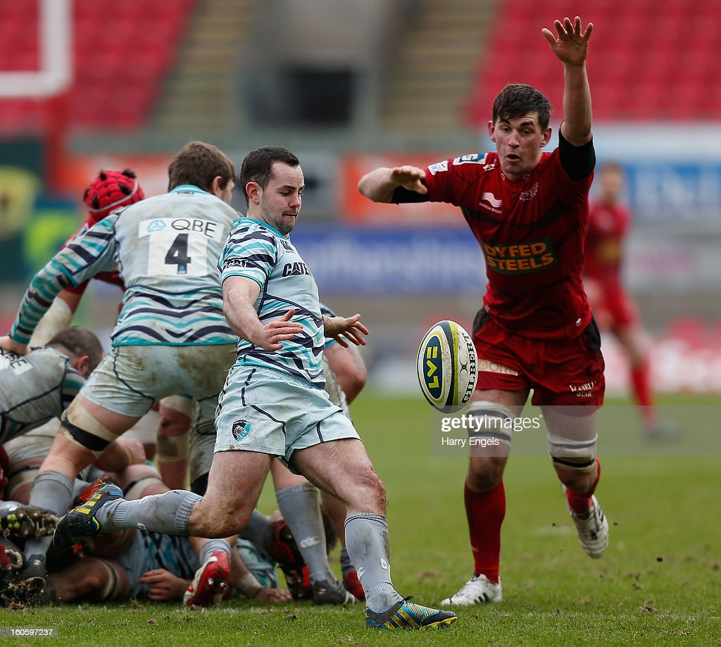 Micky Young of Leicester kicks as Lewis Rawlins of Scarlets attempts to charge down during the LV= Cup match between Scarlets and Leicester Tigers at Parc y Scarlets on February 3, 2013 in Llanelli, Wales.