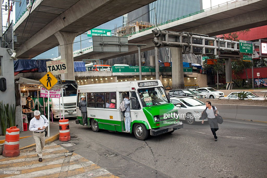 A micro bus picks up passengers in Mexico City, Mexico, on Monday, June 20, 2016. The air quality in Mexico City has risen above the government's acceptable limits triggering restrictions on automobile usage and stricter vehicle emissions testing. Photographer: Brett Gundlock/Bloomberg via Getty Images