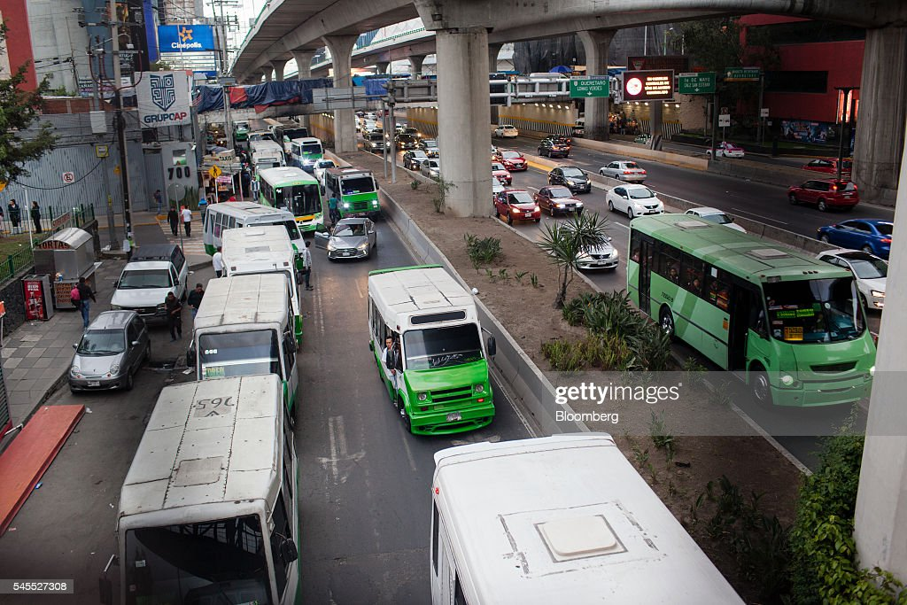 Micro buses leave a station in Mexico City, Mexico, on Monday, June 20, 2016. The air quality in Mexico City has risen above the government's acceptable limits triggering restrictions on automobile usage and stricter vehicle emissions testing. Photographer: Brett Gundlock/Bloomberg via Getty Images