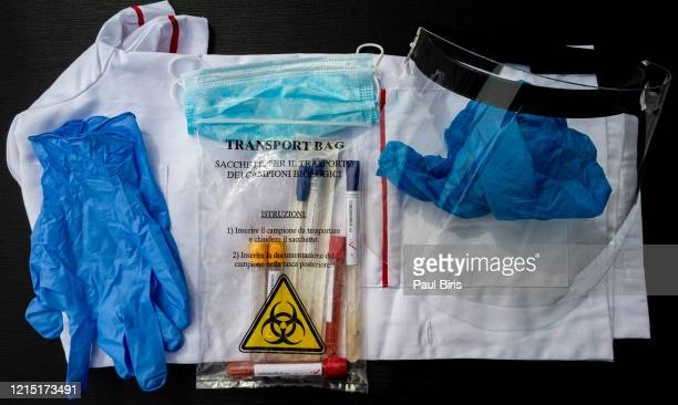 microbiologist equipment [protection against coronavirus]:plastic visor, biohazard transportation bag filled with test tubes with blood sample for covid-19 virus, gloves, face mask and costume - protective suit stock pictures, royalty-free photos & images