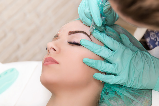 Microblading eyebrows work flow in a beauty salon. Woman having her eye brows tinted. Semi-permanent makeup for eyebrows. Focus on model's face and eyebrow 929239380