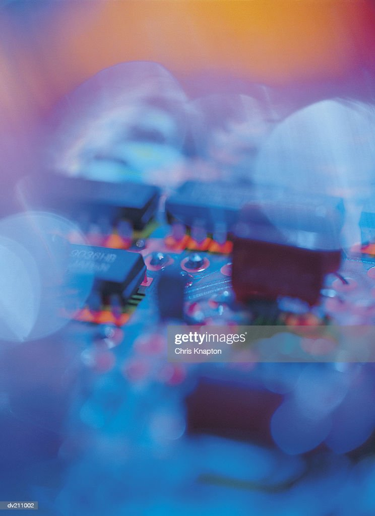 Micro-chips on a blurred and variegated circuit board : Stock Photo