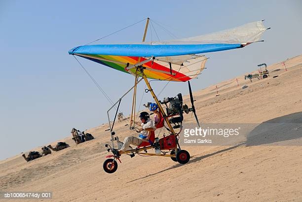 microlite plane with two passengers landing in sahara desert, side view - aereo ultraleggero foto e immagini stock