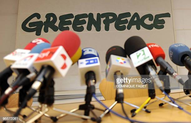 Microphes stand on a table in front of a Greenpeace logo before a press conference by Kumi Naidoo Executive Director of Greenpeace International on...