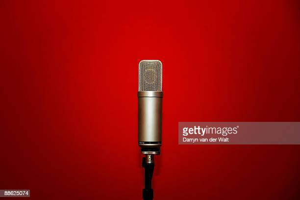 microphone against a red background - sound recording equipment stock pictures, royalty-free photos & images
