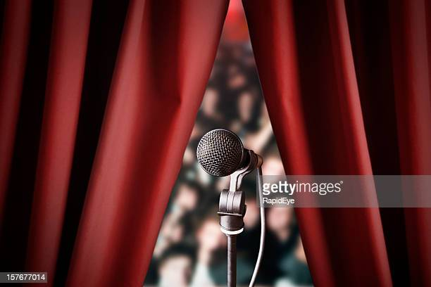 microphone and out of focus audience through red drapes - stage curtain stock pictures, royalty-free photos & images