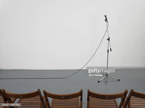 microphone before row of empty chairs - マイクスタンド ストックフォトと画像