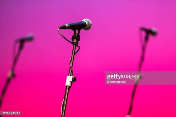microphone feet with microphones over pink and purple - música pop fotografías e imágenes de stock
