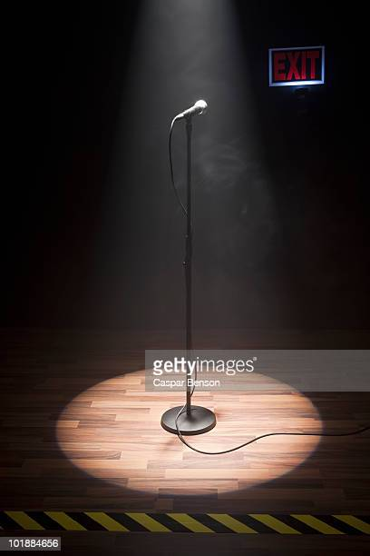 a microphone illuminated on a stage - microphone stand stock photos and pictures