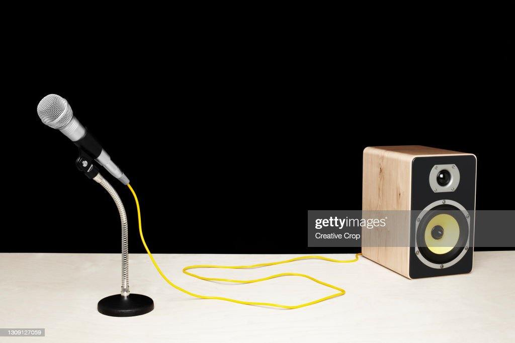 Microphone in a desktop stand connecting to a speaker on a tabletop : Stock Photo
