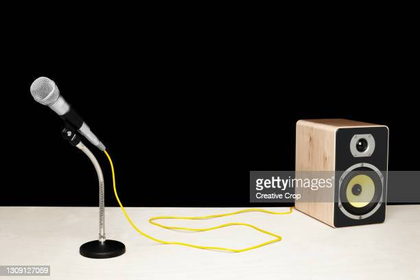 microphone in a desktop stand connecting to a speaker on a tabletop - microzoa stock pictures, royalty-free photos & images